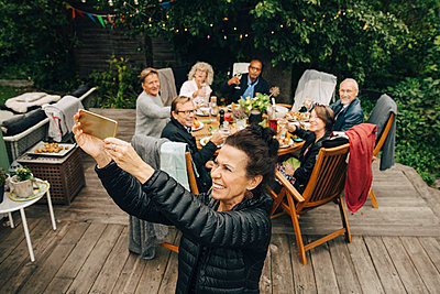 Smiling senior woman taking selfie with friends sitting at dining table in back yard during dinner party - p426m2195176 by Maskot