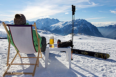 Skier relaxing with a beer. - p4295481 by Ross Woodhall