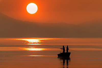 Silhouetted anglers standing in a boat fishing for salmon at sunset; Juneau, Alaska, United States of America - p442m2154344 by John Hyde