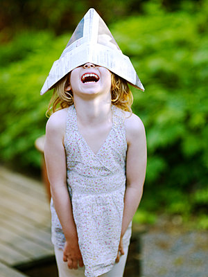 Laughing girl wearing paper hat - p528m1075317f by Anna Kern