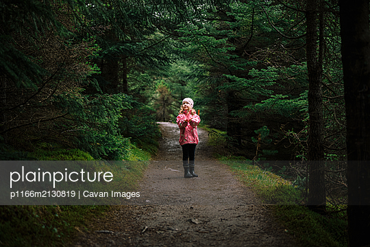 Little girl on mysterious forest trail - p1166m2130819 by Cavan Images