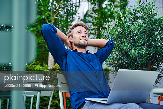 Young businessman with laptop at an outdoor cafe in the city having a break - p300m2140655 by Philipp Nemenz