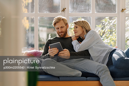 Man with wife using tablet in sunroom at home - p300m2205540 by Kniel Synnatzschke