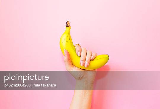 Frau hält Banane in der Hand - p432m2064239 von mia takahara