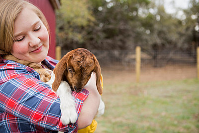 A girl cuddling a baby goat.  - p1100m923413f by Norah Levine