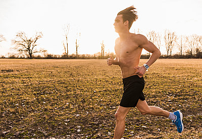 Barechested man running in rural landscape - p300m1356395 by Uwe Umstätter