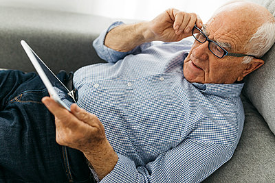 Senior man surfing the internet on a tablet while lying on the sofa - p300m2005566 by Josep Rovirosa