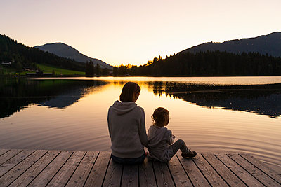 Mother and little daughter sitting together at end of lakeshore jetty at dusk - p300m2242420 by Daniel Ingold