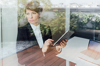Contemplating businesswoman holding digital tablet while looking through window seen through glass - p300m2276235 by Eugenio Marongiu