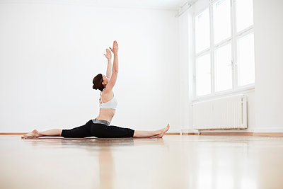Side view of woman in exercise arms raised doing the splits - p429m1179763 by Stephen Lux