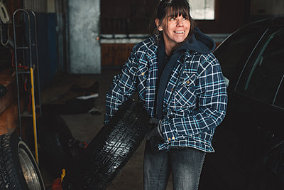 Woman carrying tyre in workshop - p924m1224700 by Kymberlie Dozois Photography