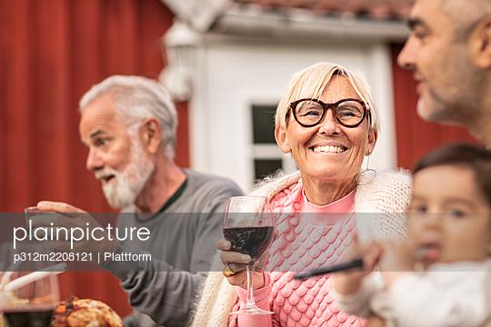 Happy woman sitting at table - p312m2208121 by Plattform