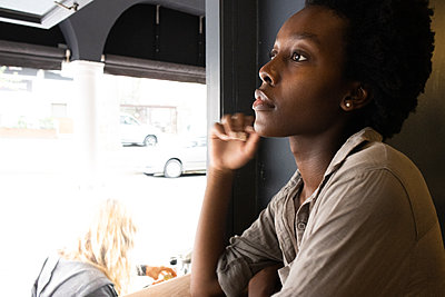 Young African woman at the window in a bistro - p1640m2260111 by Holly & John