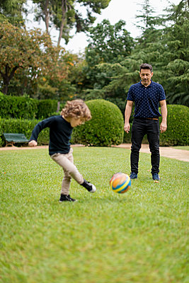 Father and son playing football in park - p300m2080909 von Mauro Grigollo
