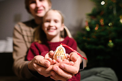 Father and daughter showing golden Christmas ornament - p300m2160436 by Ekaterina Yakunina
