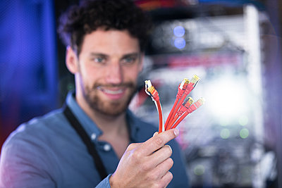 Smiling male IT professional with patch cord cable standing in data center - p300m2274468 by Florian Küttler