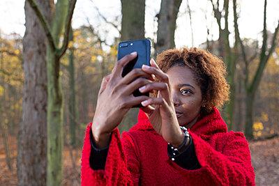 Dark-skinned woman takes a selfie on the edge of woods - p975m2228542 by Hayden Verry