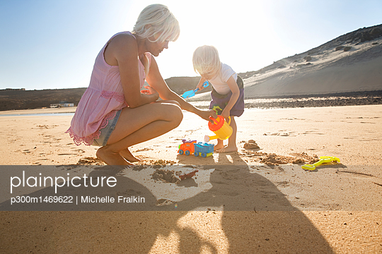 Spain, Fuerteventura, mother and daughter playing on the beach - p300m1469622 by Michelle Fraikin