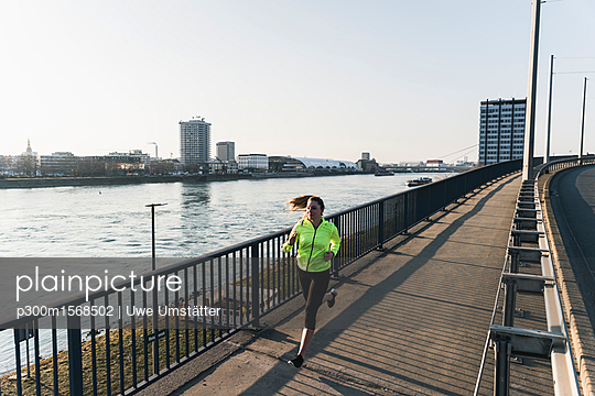 Young woman running on bridge at the riverside - p300m1568502 by Uwe Umstätter