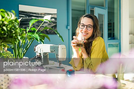 Portrait of content fashion designer sitting at desk in her studio with drink - p300m1581596 von Robijn Page