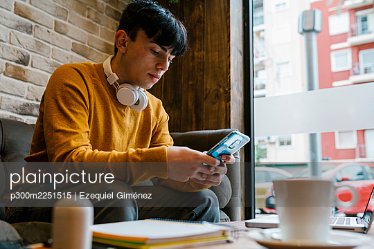 Young man with headphones using mobile phone while sitting at cafe - p300m2251515 by Ezequiel Giménez