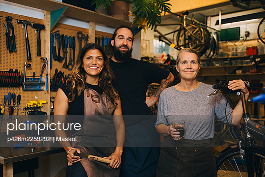 Portrait of smiling colleagues in bicycle workshop - p426m2259292 by Maskot