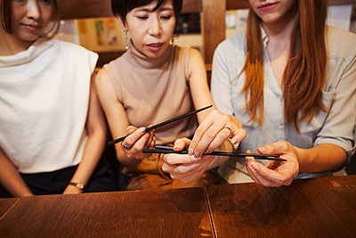 Three women sitting side by side at a table in a restaurant, holding chopsticks. - p1100m1531117 by Mint Images