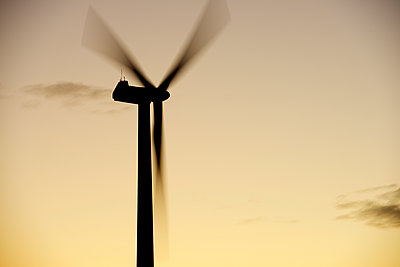 Low angle view of silhouette windmill spinning against sky during sunset - p1166m1545182 by Cavan Social