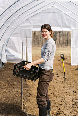A young female farmer working in green house in the morning in spring - p1166m2269691 by Cavan Images