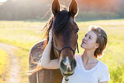 Young woman and horse in nature - p300m1460580 by Tom Chance