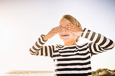 Happy boy on the beach covering his eyes - p300m2167548 by Floco Images