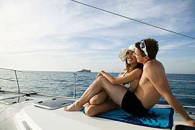 A couple sunbathing together on a yacht - p3018624f by Antenna