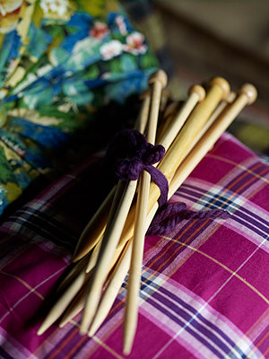 Bundle of knitting needles on pink tartan. - p349m2167771 by Polly Wreford
