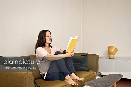 Brunette woman on sofa reading book - p294m2132890 by Paolo