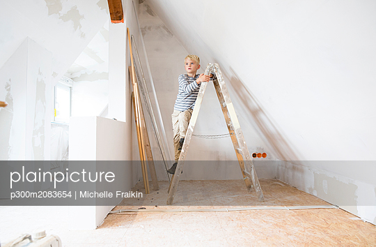 Boy standing on ladder in attic to be renovated - p300m2083654 by Michelle Fraikin