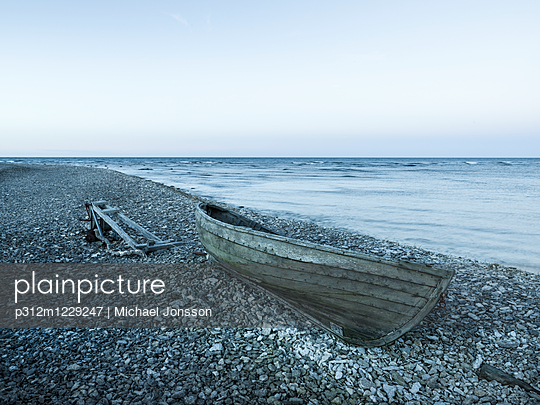 Rowing boat on pebble beach - p312m1229247 by Michael Jonsson