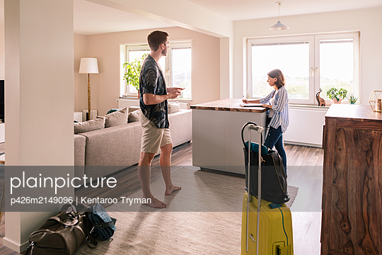 Woman filling form while man using phone at house rental during staycation - p426m2149096 by Kentaroo Tryman