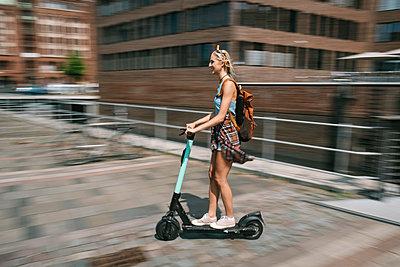 Junge Frau unterwegs mit dem E-Scooter - p299m2108617 von Silke Heyer