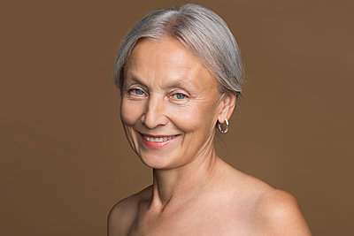 Portrait of naked senior woman with grey hair in front of brown background - p300m2043180 von Vladimir Godnik