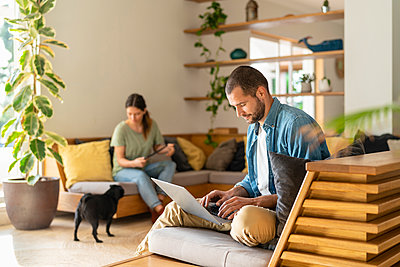 Young man working on laptop while wife looking at Pug dog in background at home - p300m2267390 by Steve Brookland