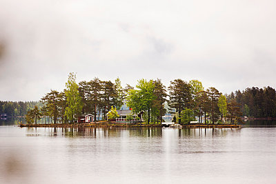 Trees and houses on small island - p312m970981f by Per Eriksson