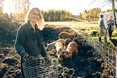 Portrait of smiling female farmer holding empty basket with pigs grazing at organic farm - p426m1537113 by Maskot