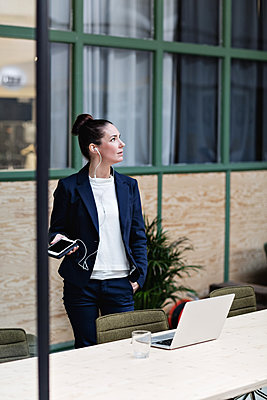 Businesswoman talking through headphones on mobile phone by table at office - p426m1579907 by Maskot