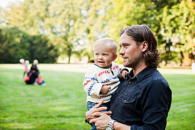 Father carrying happy baby girl in park - p426m977508f by Astrakan