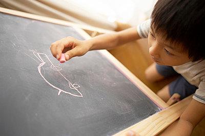 Boy drawing on blackboard - p5143212f by Doable