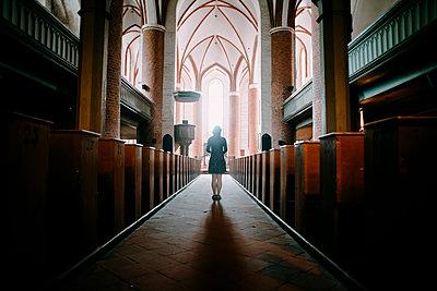 Caucasian woman standing in aisle of church - p555m1444038 by Alexey Karamanov
