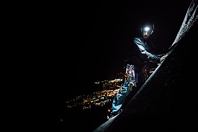 A man trad climbing at night with helmet and headlight, Squamish, British Columbia, Canada - p924m2165222 by Alex Eggermont