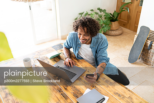 Businessman holding smart phone while using laptop on table at home - p300m2277593 by Steve Brookland