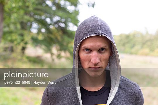 Junger Mann in Kapuzenshirt, Portrait - p975m2215848 von Hayden Verry