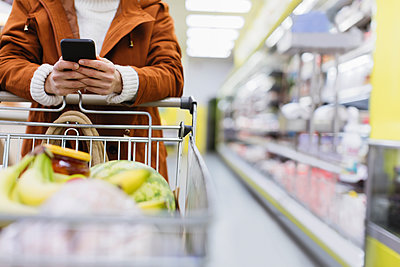 Woman with smart phone pushing shopping cart in supermarket - p1023m2187662 by Sam Edwards